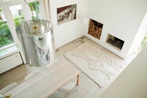 Белый прямоугольный вязаный коврик возле камина