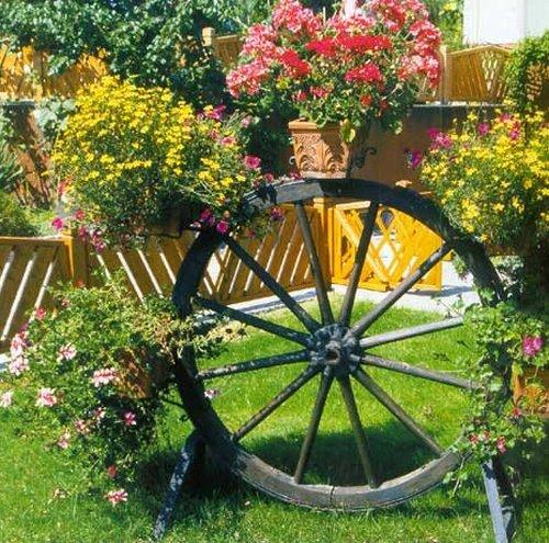 Цветы в горшках на колесе от телеги