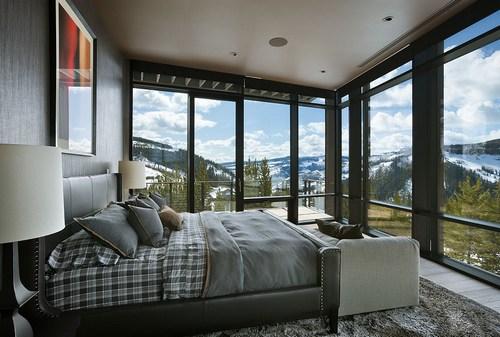 Дом в горах - интерьер спальни с большими окнами