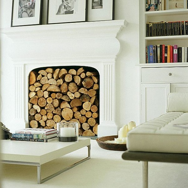 Декоративный фальш-камин с дровами в интерьере гостиной