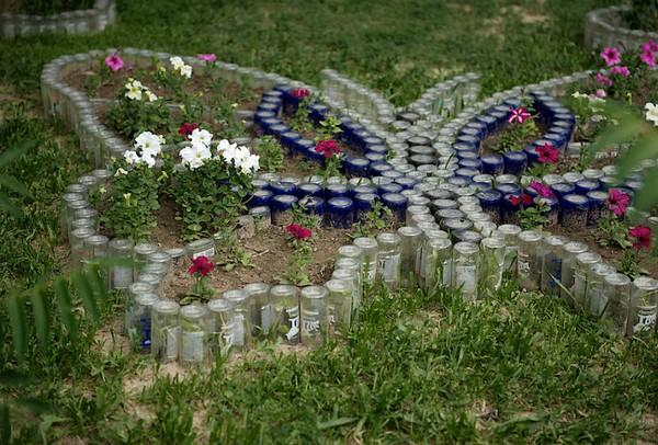 Ограждение для цветника в форме бабочки из стеклянных бутылок