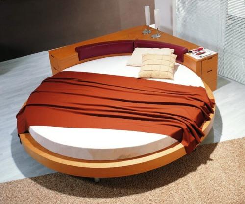 Круглая кровать с прикроватной тумбочкой.