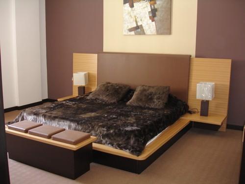 Красивая кровать с подиумом в интерьере спальни.