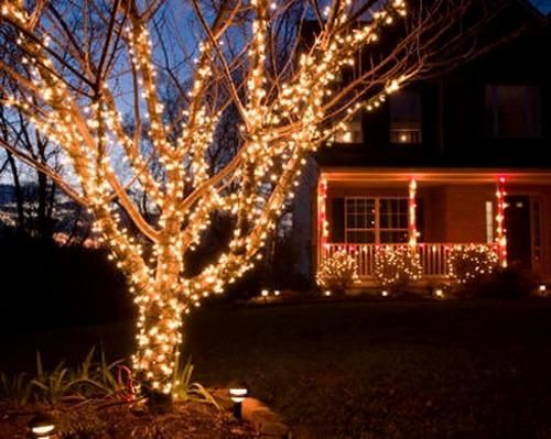 Новогоднее украшение дерева во дворе электрическими гирляндами