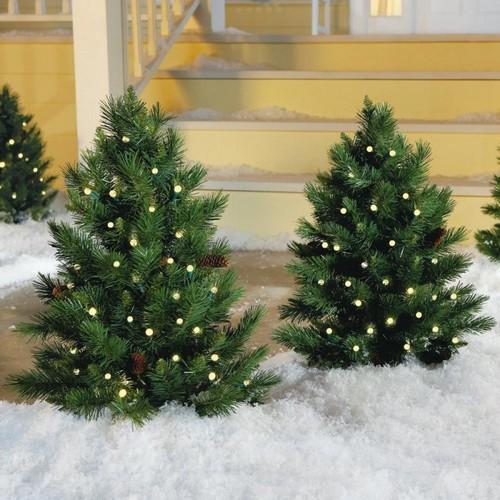 Маленькие елки во дворе с гирляндами