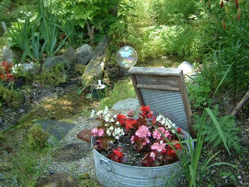 Цветник в саду в старом ведре фото