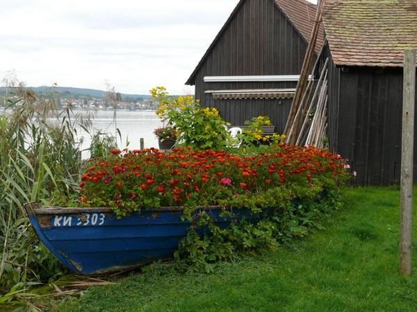 Использование старой лодки под клумбу