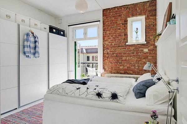 Кирпичная стена в интерьере скандинавской спальни